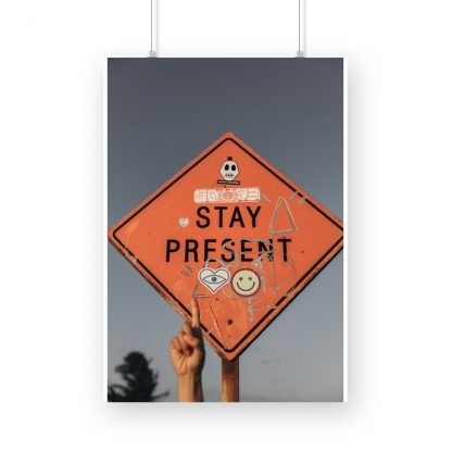 motivational poster with hand pointing to sign saying 'Stay Present' in sky background