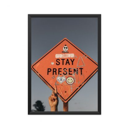 framed motivational poster with hand pointing to sign saying 'Stay Present' in sky background