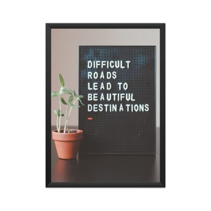 "Black framed Text "" Difficult roads lead to beautiful destinations"" on black background, next to a plant."