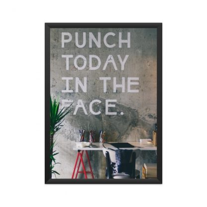 """black framed text on wall in white chalk saying """"punch today in the face"""" surrounded by plants and a desk"""
